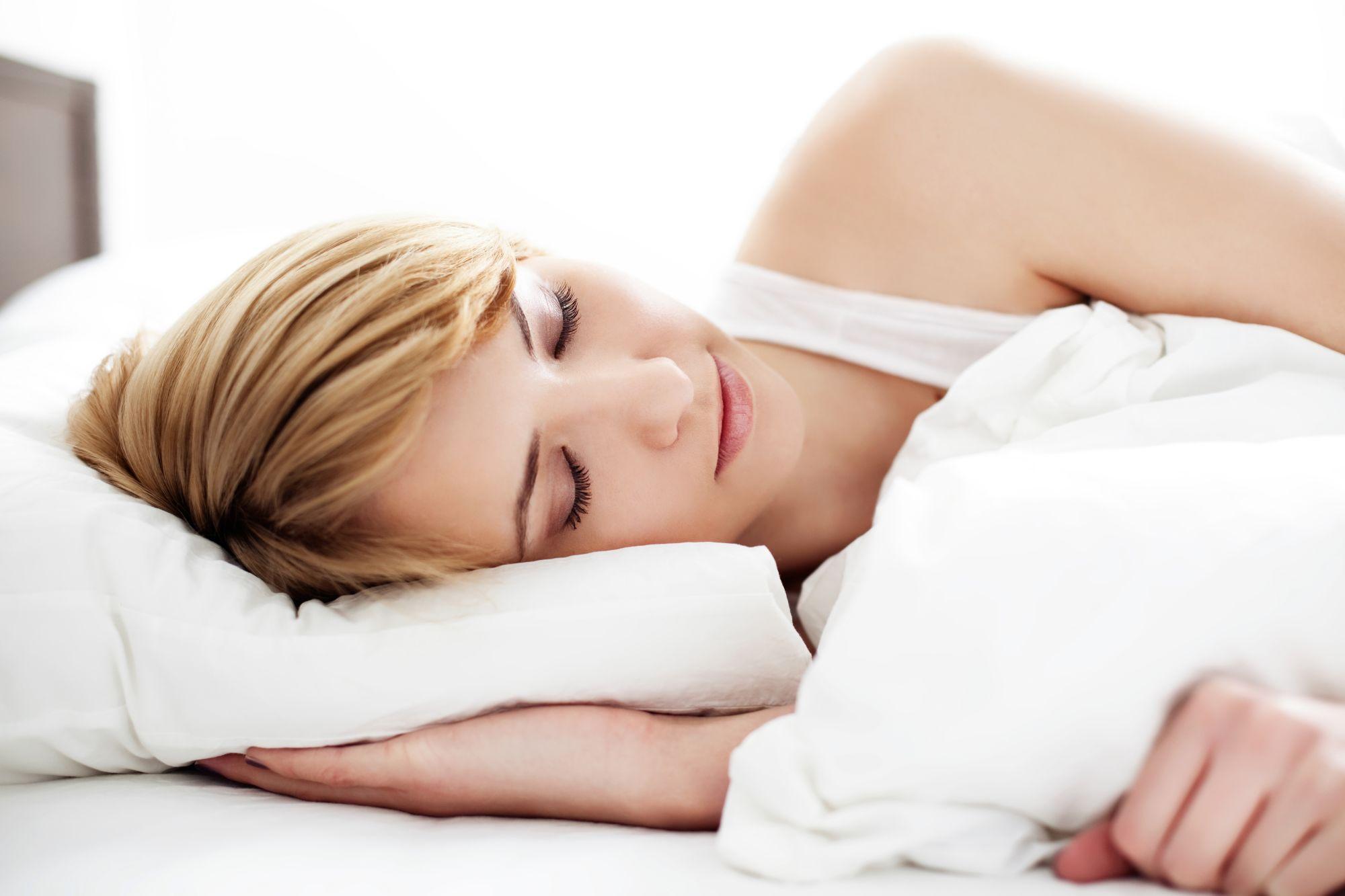 kobieta śpiąca w białej pościeli