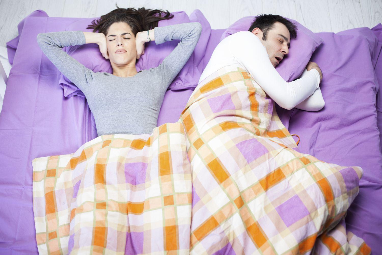 para leży w łóżku, mąż chrapie