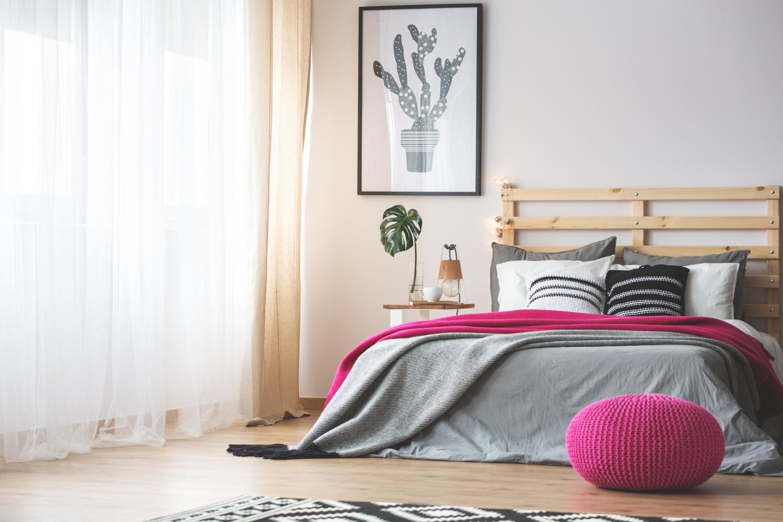 sypialnia z łóżkiem z różową narzutą