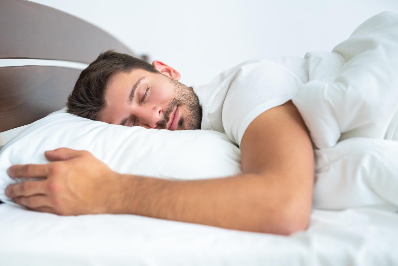 śpiący mężczyzna w białej pościeli