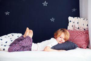 ile snu potrzebują dzieci, chłopiec leżący dla łóżku