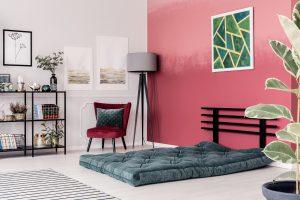 materac na podłodze w pokoju z różową ścianę, fotelem, lampą i obrazem