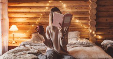8 dobrych nawyków przed snem, kobieta siedząca na łóżku i czytająca książka