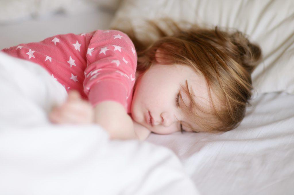jak ułatwić dziecku sen, śpiąca dziewczynka w różowej piżamie