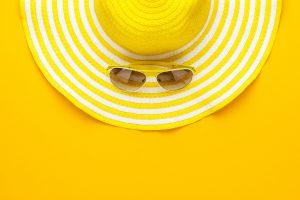 materac idealny na lato, kapelusz i okulary na żółtym tle