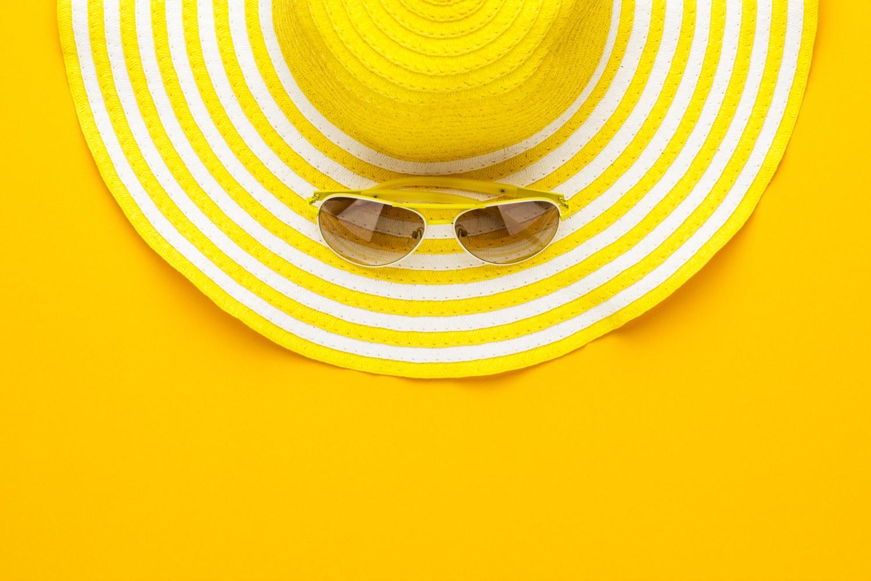 materac na lato, kapelusz i okulary na żółtym tle