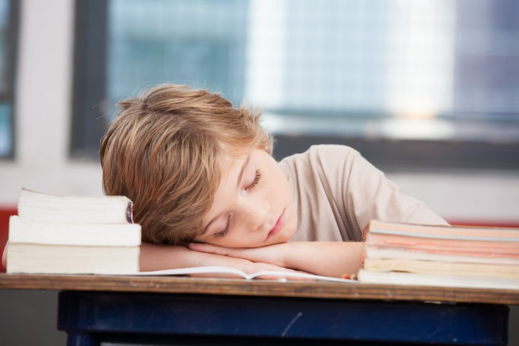 dziecko śpiące na biurku, czy szkoła i praca powinny zaczynać się po 10 rano