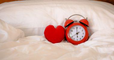 brak snu skutki, niedobór snu na serce, sercu u budzik leżące na łóżku