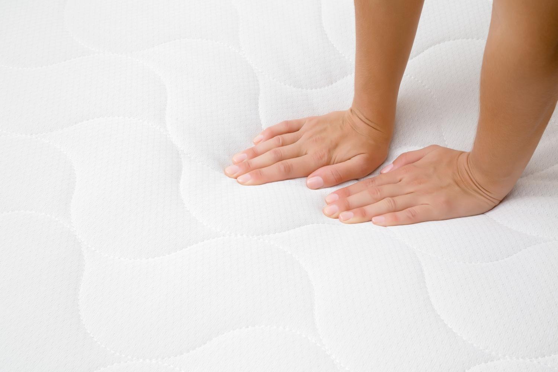 materac sprężynowy, ręka naciskająca na materac